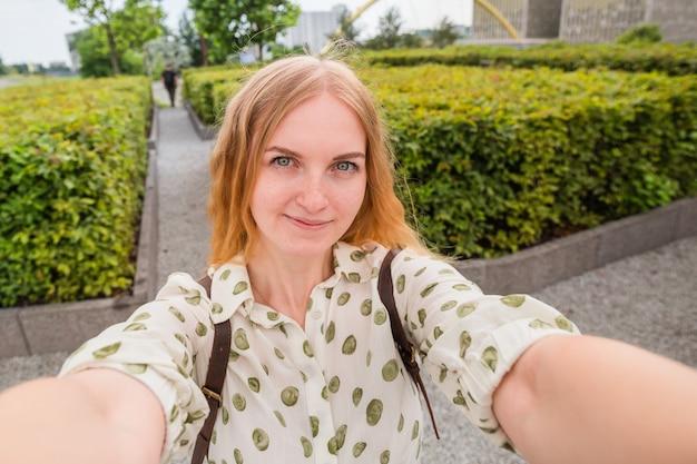 Красивая молодая женщина со светлыми волосами, делающая селфи на фоне городской улицы
