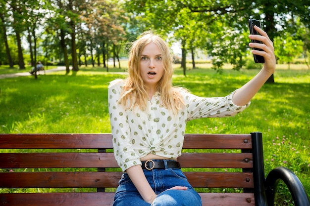 Beautiful young woman with blonde hair taking selfie at the city park