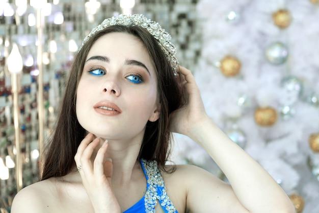 Красивая молодая женщина с голубыми глазами в короне и праздничном синем платье позирует на фоне новогодних украшений. chrismas принцесса перед белой украшенной елкой.