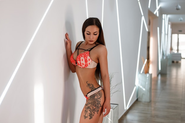 Beautiful young woman with a body with a tattoo in lingerie near a wall with light