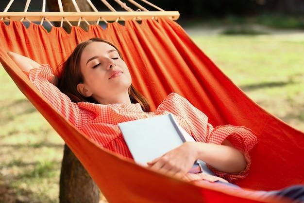 야외에서 해먹에서 쉬고 책을 가진 아름 다운 젊은 여자