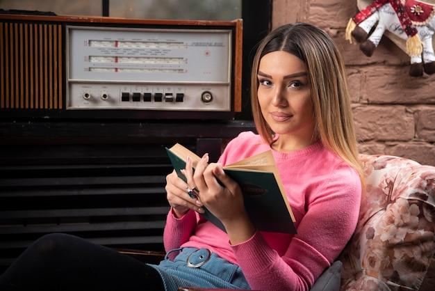 本を持つ美しい若い女性