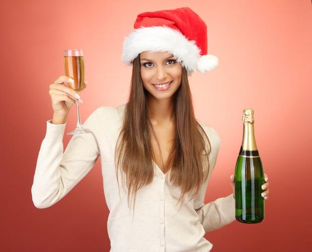 Красивая молодая женщина с бутылкой и бокалом шампанского, на красном фоне