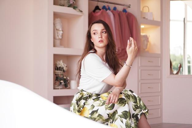 自宅で香水のボトルを持つ美しい若い女性-ピンクの楽屋