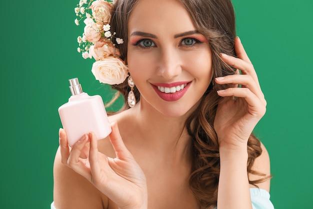 緑の香水のボトルを持つ美しい若い女性