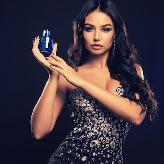 Beautiful young woman with bottle of perfume on dark space