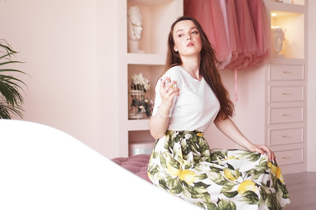 Beautiful young woman with bottle of perfume at home - pink dressing room