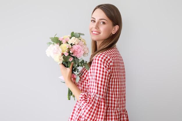 光のカーネーションの花の花束を持つ美しい若い女性