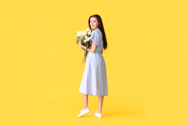 色の背景にバラの花束を持つ美しい若い女性