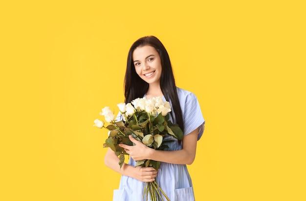 色空間にバラの花束を持つ美しい若い女性