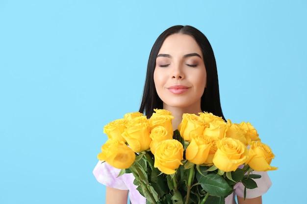 色の表面にバラの花束を持つ美しい若い女性