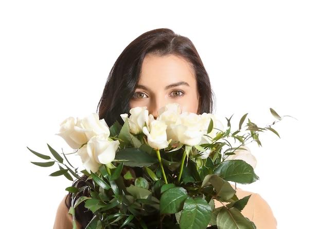 白のバラの花束を持つ美しい若い女性