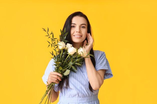 バラの花束を持つ美しい若い女性