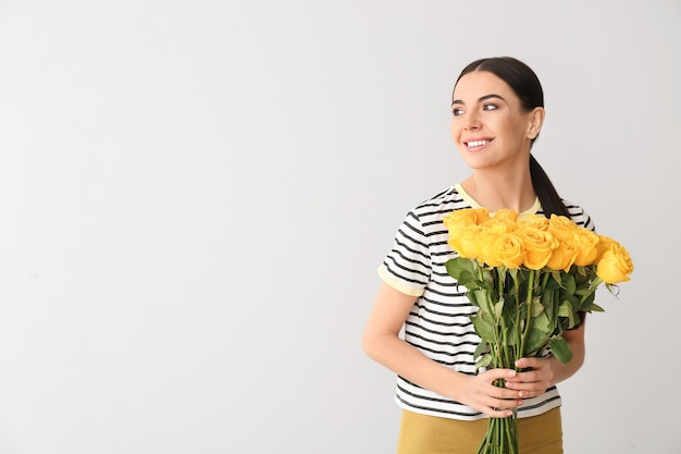 Beautiful young woman with bouquet of roses on grey surface