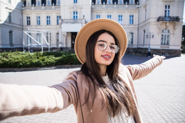 Beautiful young woman with braces make selfie during sunny day