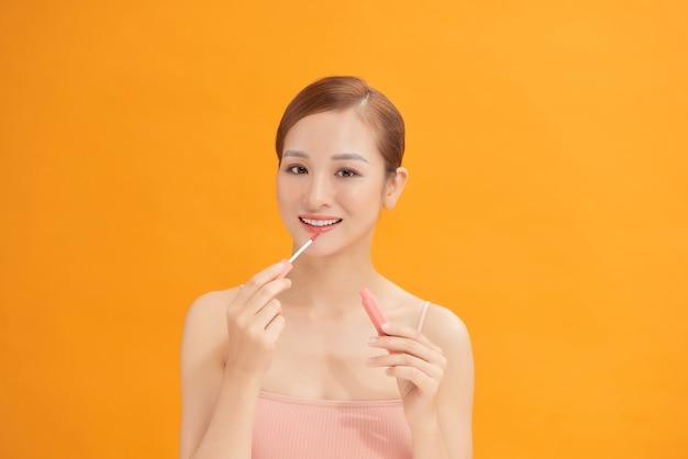 黄色の壁に明るい口紅を持つ美しい若い女性
