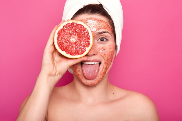 Beautiful young woman with bright scrub on her face holds half of rape grapefruit in one hand, sticks out her tongue, having white towel on her head, looks fresh and delighted. skin care concept.