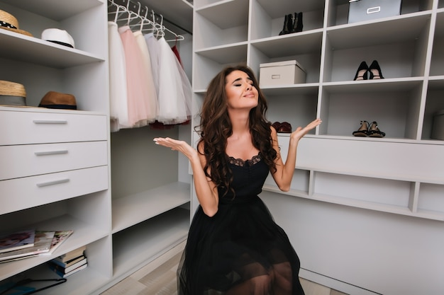 Beautiful young woman with brown curly hair sitting in dressing room, wardrobe, disappointed, upset, hard to make choice, nothing to wear. model wearing black fancy dress, elegant look.