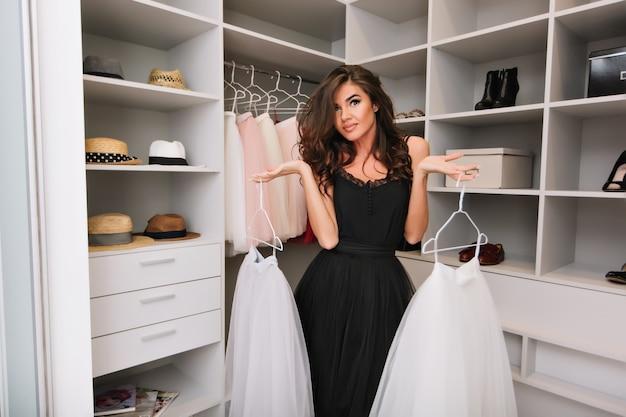 Красивая молодая женщина с каштановыми длинными вьющимися волосами в красивом гардеробе вокруг одежды, головных уборов, обуви, держит белые пушистые юбки, решая, что надеть.