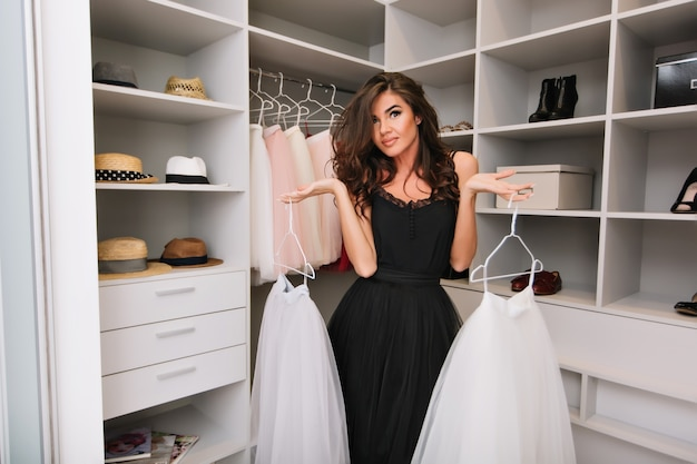 Beautiful young woman with brown long curly hair in nice wardrobe around clothes, hats, shoes, holding white fluffy skirts, deciding what to wear.