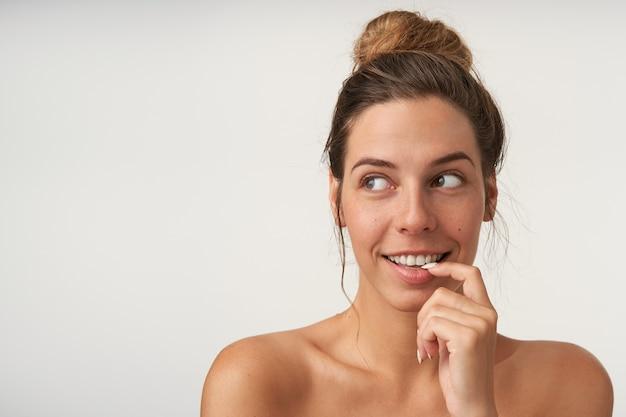 お団子の髪型がふざけて脇を見て、笑顔で人差し指を下唇に保ち、白の上に立っている美しい若い女性