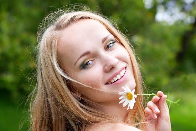 Beautiful young woman with camomile, summer day