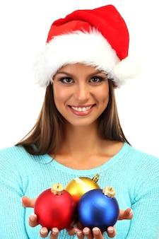 孤立したクリスマスボールを持つ美しい若い女性
