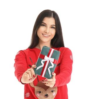 白のクリスマス プレゼントを持つ美しい若い女性