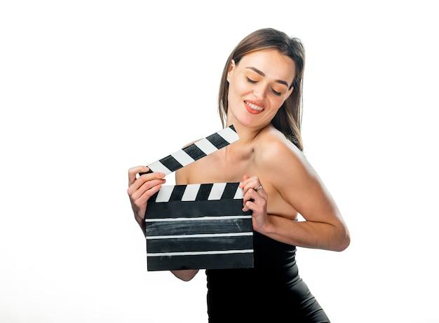 스튜디오에서 포즈를 취하는 영화 클래퍼와 함께 아름 다운 젊은 여자. 영화 개념입니다. 외딴.