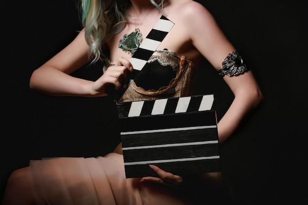 Красивая молодая женщина с трещоткой кино позирует в студии