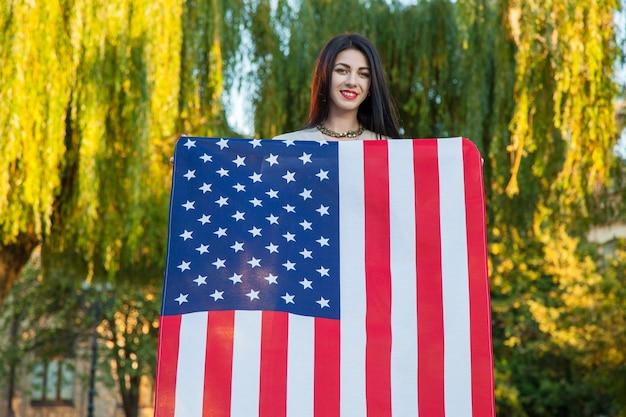 Красивая молодая женщина с классическим платьем, держащая американский флаг в парке, фотомодель, держащая нас