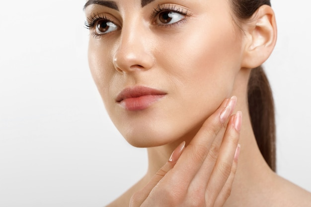 Beautiful young woman with clean fresh skin applying cream
