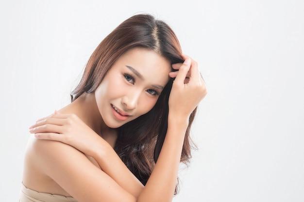 Красивая молодая женщина с чистой свежей кожей. жесты для рекламы на сером фоне, вид спереди, с копией пространства.