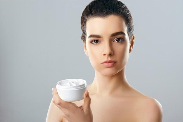 병을 들고 깨끗 하 고 신선한 피부와 아름 다운 젊은 여자. 뷰티 페이스 케어. 페이셜 트리트먼트.