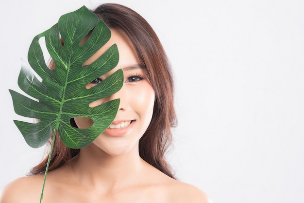Beautiful young woman with clean fresh skin holding green leaf