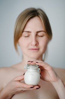 A beautiful young woman with clean fresh skin holds a white jar with a face cream