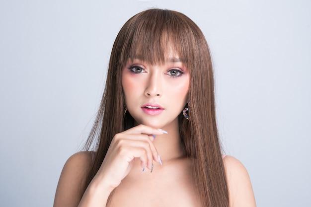 Красивая молодая женщина с чистой свежей кожей, гладкими длинными волосами, изолированными на сером фоне. с копией пространства.