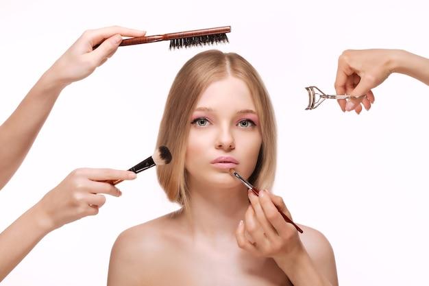 공백에 광고 메이크업 브러시 제스처와 함께 제품을 제안하는 깨끗하고 신선한 피부를 가진 아름 다운 젊은 여자
