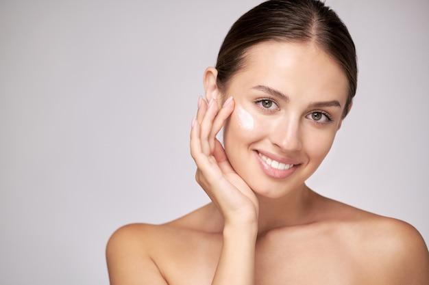 Красивая молодая женщина с чистой свежей кожей, стоящая на светло-сером фоне
