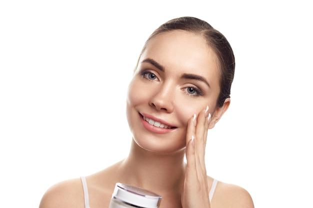 清潔でフレッシュな肌の美しい若い女性が自分の顔に触れ、保湿クリームを保持します。美顔術。美容とスパ。スキンケア。化粧品。