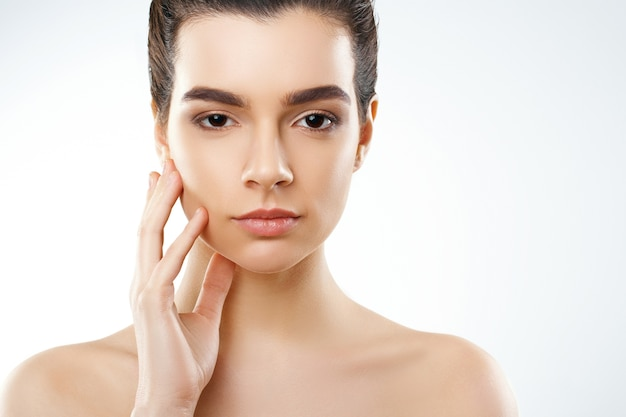 Beautiful young woman with clean fresh skin touch own face. cosmetology, beauty