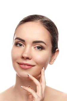 きれいな新鮮な肌を持つ美しい若い女性は自分の顔に触れます。美顔術。美容とスパ。スキンケア。化粧品、メイクアップ、