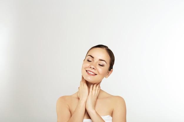 깨끗하고 신선한 피부를 가진 아름 다운 젊은 여자는 자신의 얼굴을 만집니다. 페이셜 트리트먼트. 미용, 미용 및 스파. 피부 관리. 자연스러운 메이크업으로 모델
