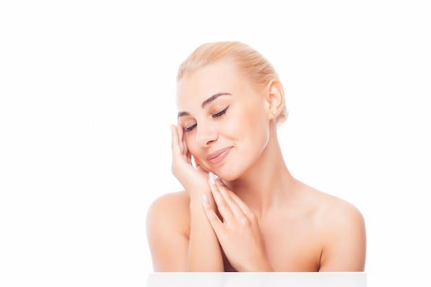 清潔でさわやかな肌を持つ美しい若い女性は自分の顔に触れます。フェイシャルトリートメント 。美容、美容、スパ。