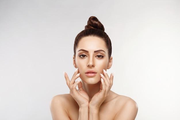 깨끗하고 신선한 피부를 가진 아름 다운 젊은 여자는 자신의 얼굴을 만집니다. 페이셜 트리트먼트. 미용, 미용 및 스파.