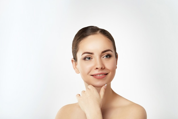 Beautiful young woman with clean fresh skin touch own face. facial treatment. cosmetology, beauty and spa. skin care. model with natural makeup