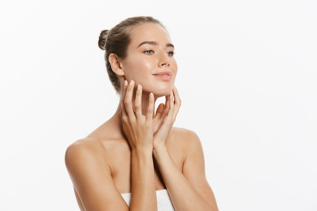 Beautiful young woman with clean fresh skin touch own face. facial treatment.