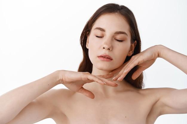 La bella giovane donna con la pelle pulita e fresca tocca il proprio viso