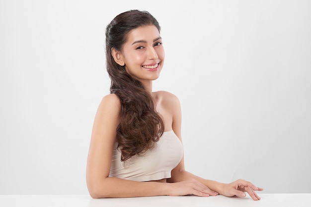 Beautiful young woman with clean fresh skin on white wall