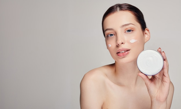 Beautiful young woman with clean fresh skin. woman holding cream in her left hand on white. spa and care concept.
